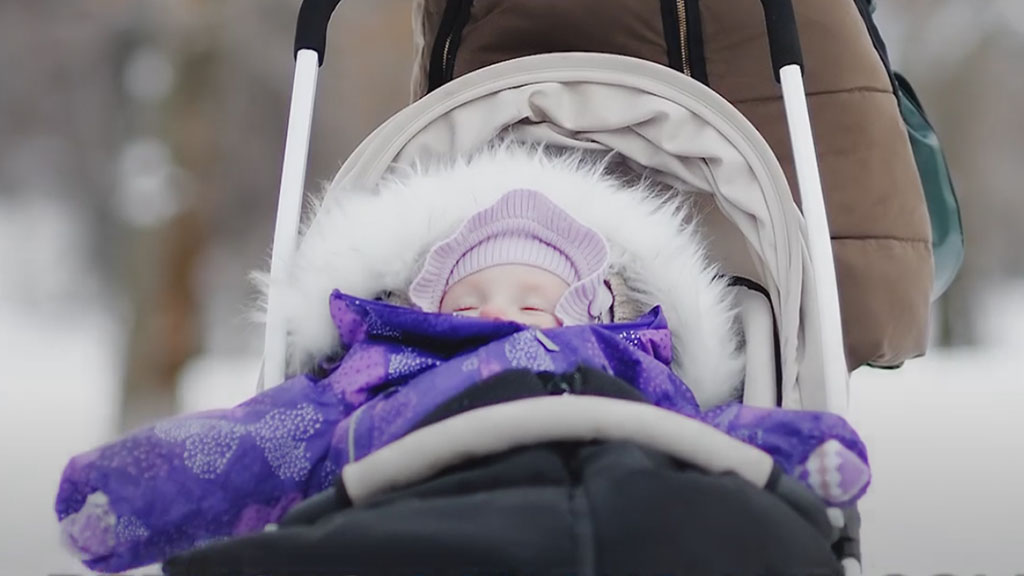 A baby sleeps in a stroller in the snow