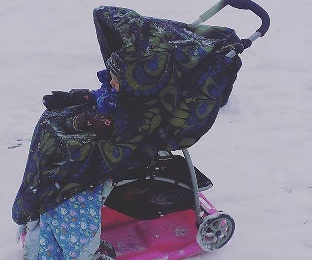 A baby sleeps in an unaccompanied stroller.