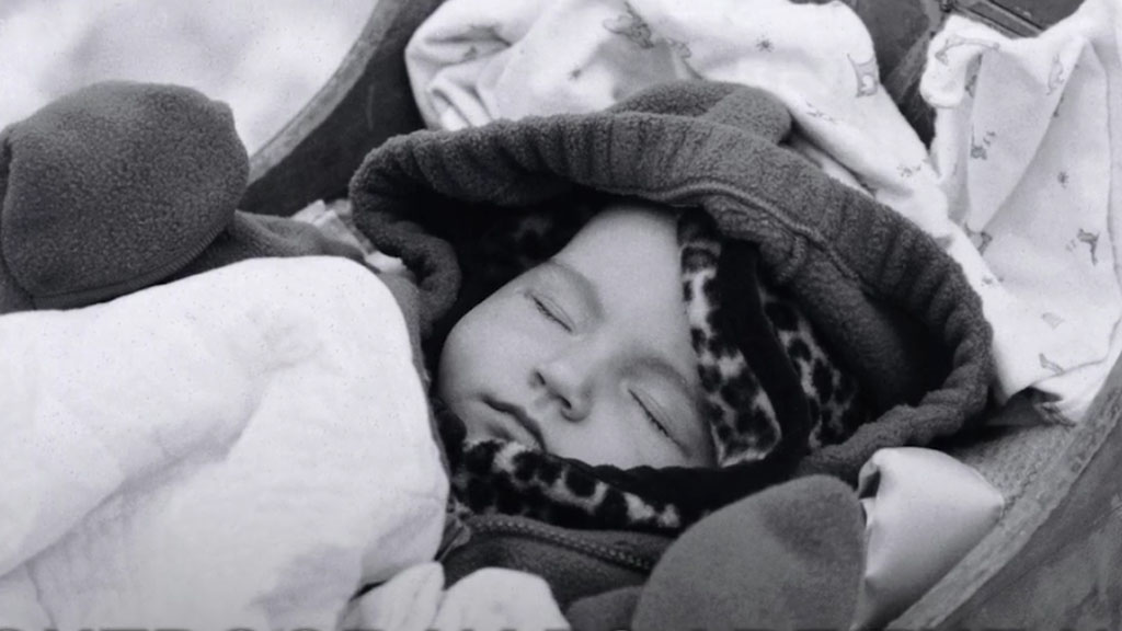 A bundled baby naps outside in cold temperatures.
