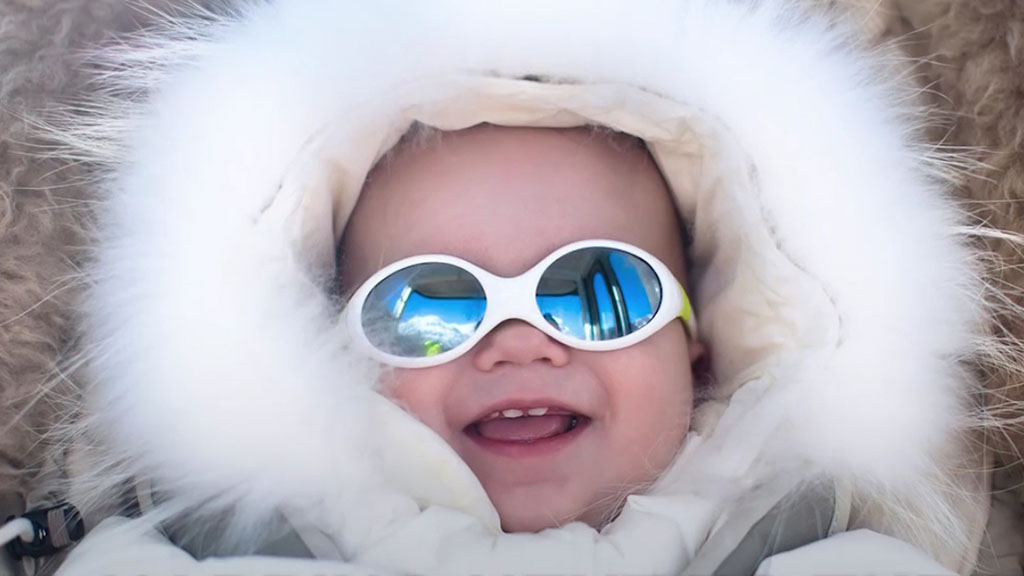 A baby with sunglasses smiles while wearing a large, fluffy snow jacket