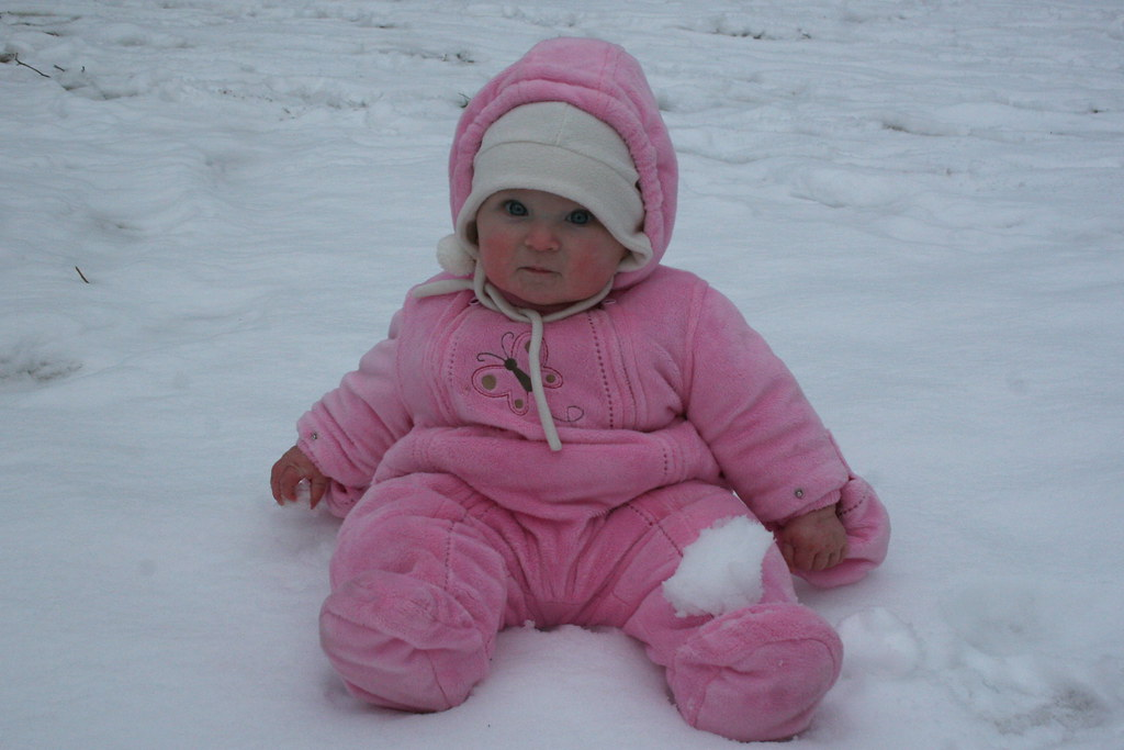 A baby in a thick, pink onesie sits in the snow.