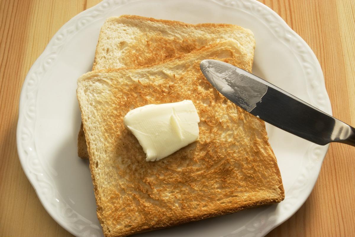 Ernaehrung, Fruehstueck: Zwei Scheiben Toastbrot mit Butter auf einem Teller