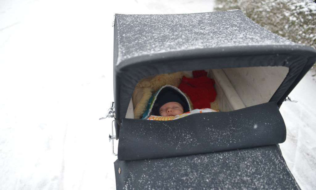 A baby naps outside in a snow-dusted stroller
