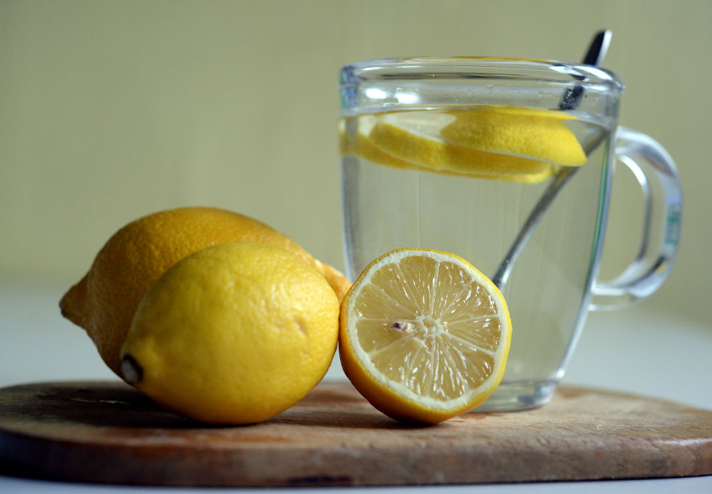 A glass of lemon water is pictured near sliced lemons