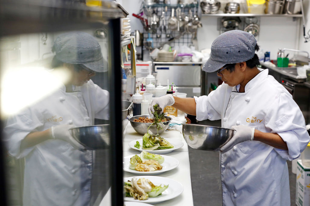A chef places toppings onto plates of salad
