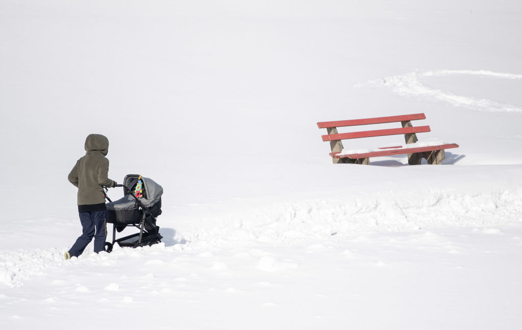 A woman pushes a stroller through dense, smooth snow
