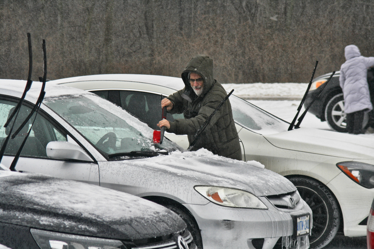 Man scrapes ice from his windshield as snow, freezing rain and ice pellets hit the Greater Toronto Area