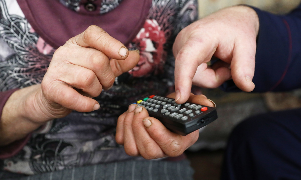 An elderly woman uses a remote control after installing a digital TV receiver