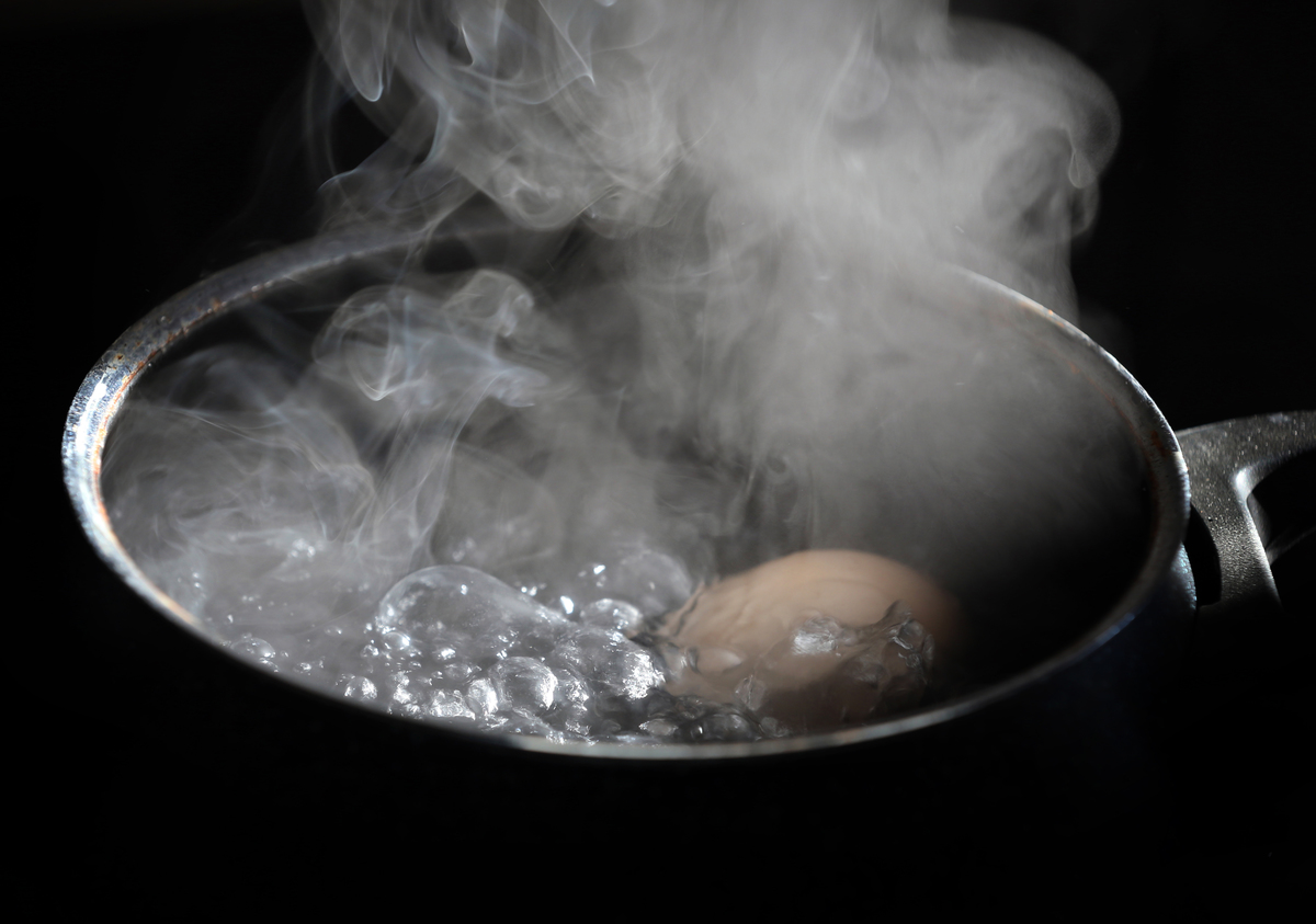 An egg lies in a pot on a hotplate in boiling water.