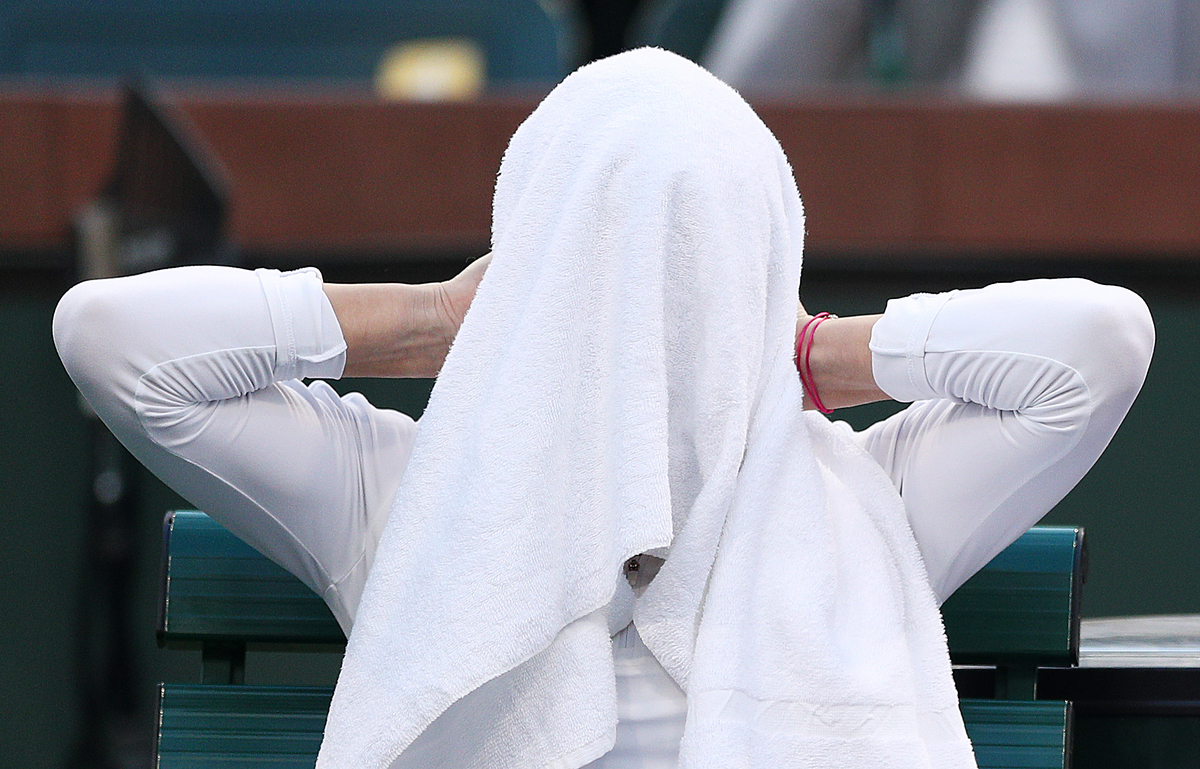 Simona Halep of Romania covers her face with a towel