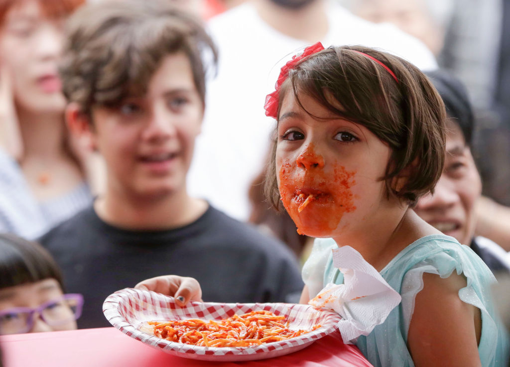 A young girl eating pasta wears sauce all over her mouth