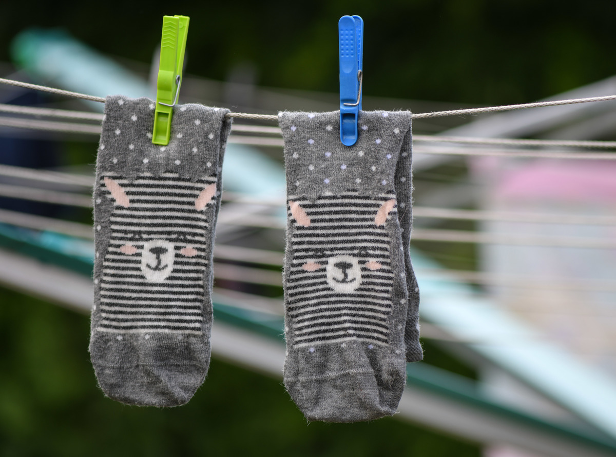 Freshly washed lama socks of a child hang on a clothes horse