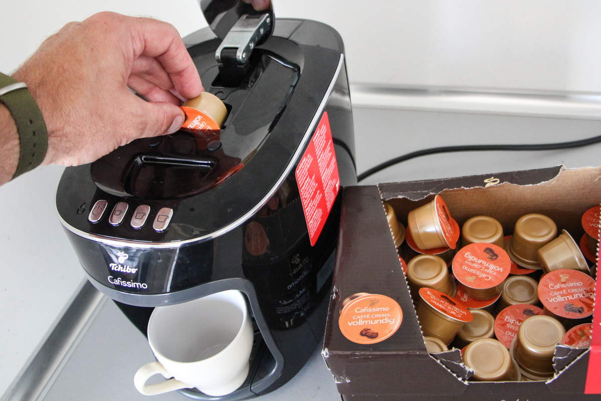 Man puts coffee capsule into a coffee maker