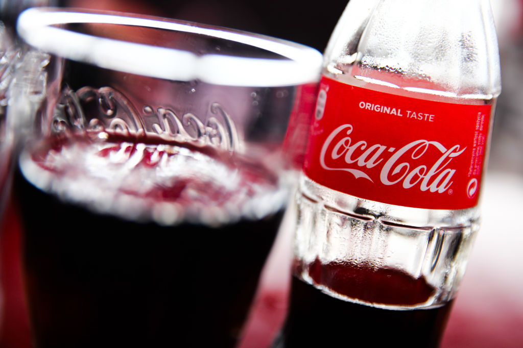A bottle of Coca-Cola sits next to a glass