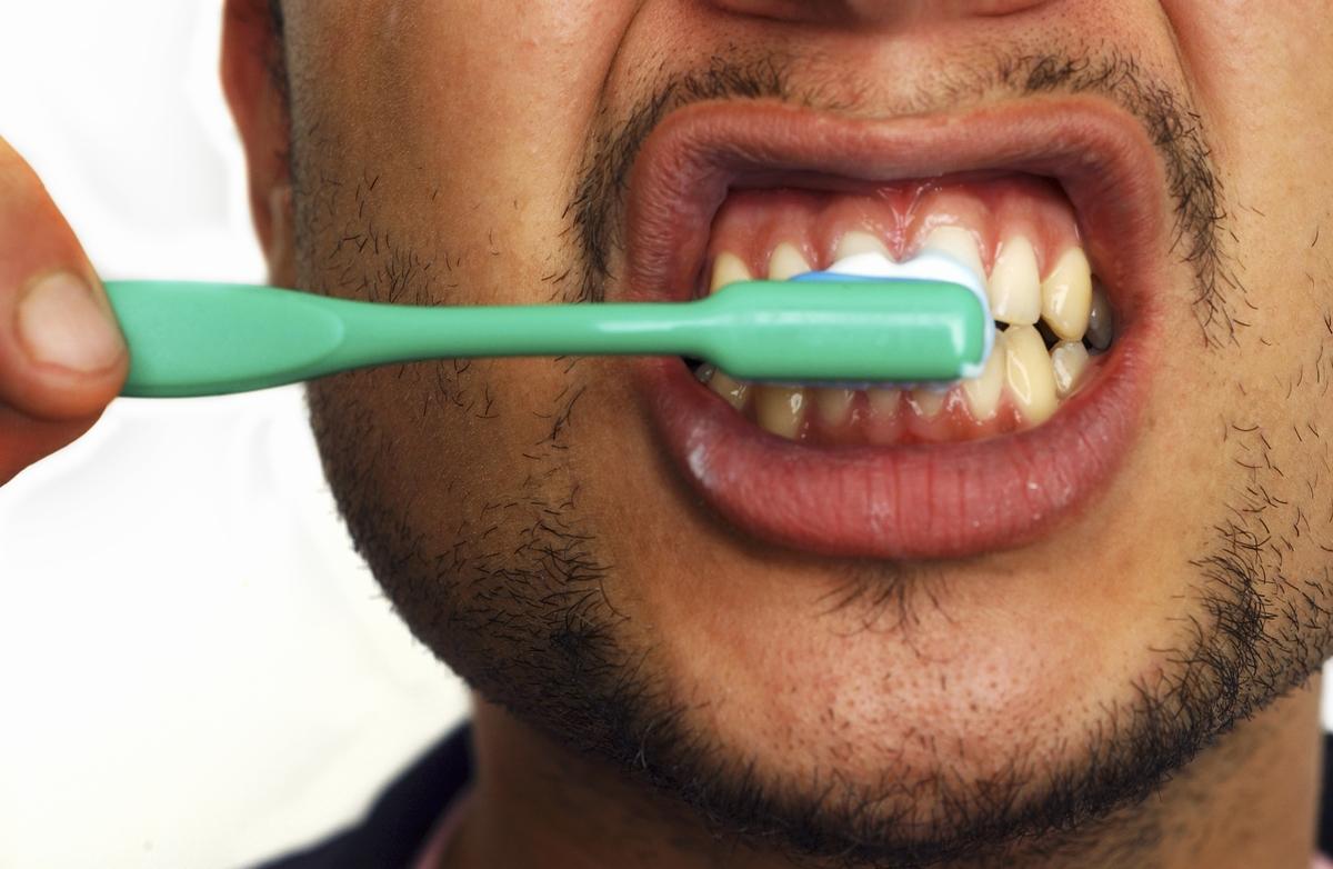 Close-up of young man brushing his teeth