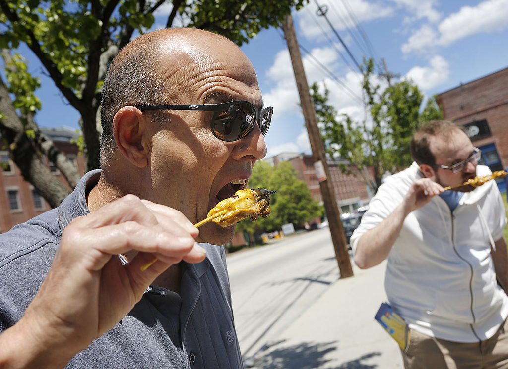 A man bites into a dogfish skewer