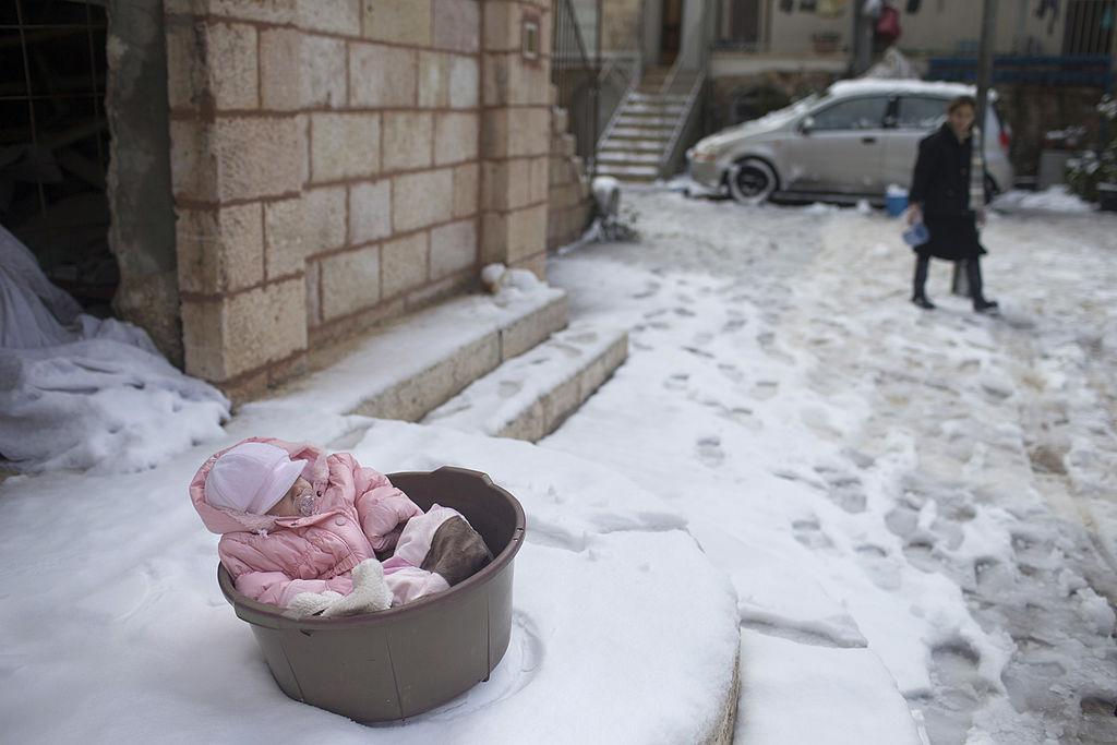 A bundled baby sleep in a pail on a snowy doorstep