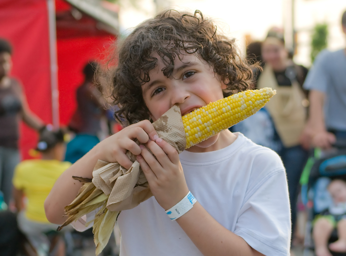 Child boy eating hot corn on a holiday in the city.