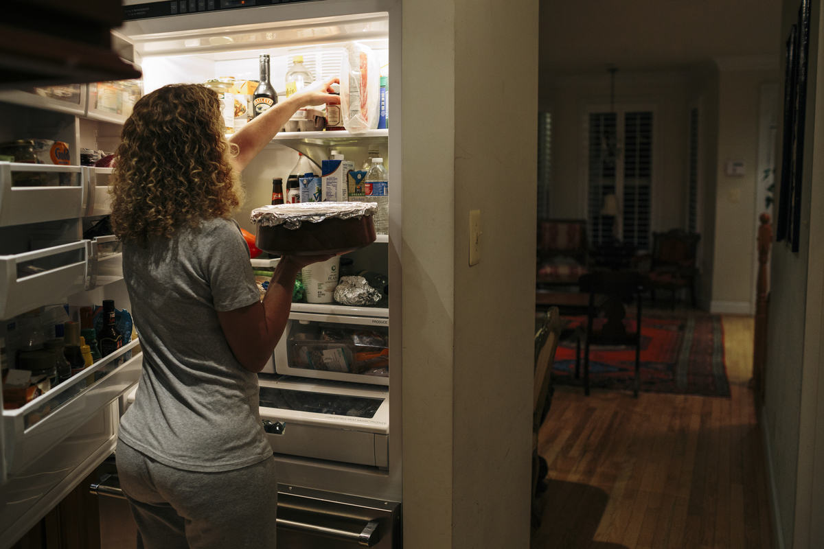 Debbie Wasserman Schultz places roasted brussel sprout and pomegranate quinoa in the refrigerator at the home