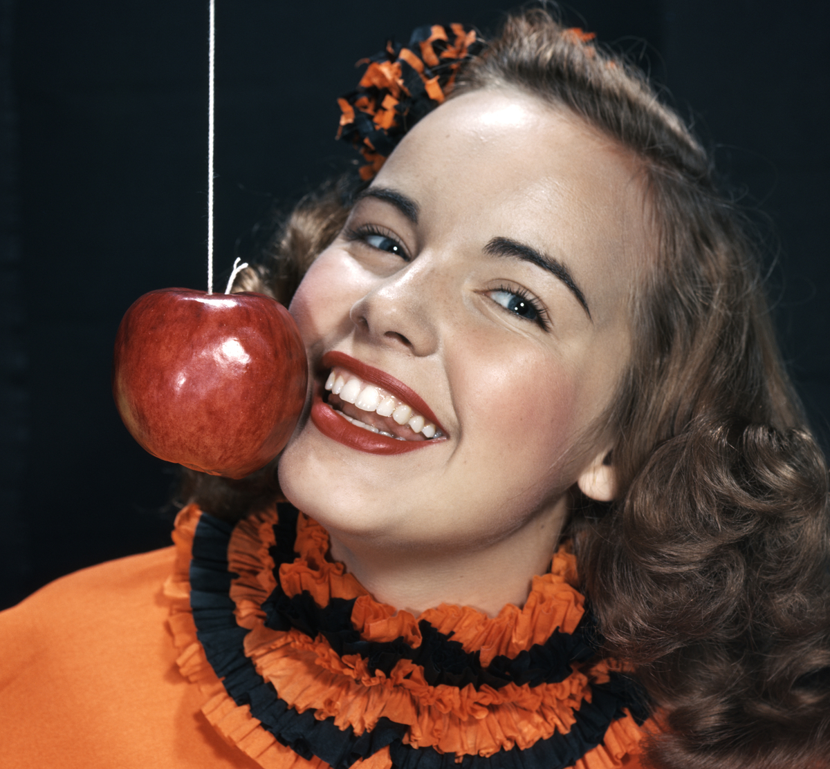 Girl eating apple on a string, Los Angeles, California, 1949.