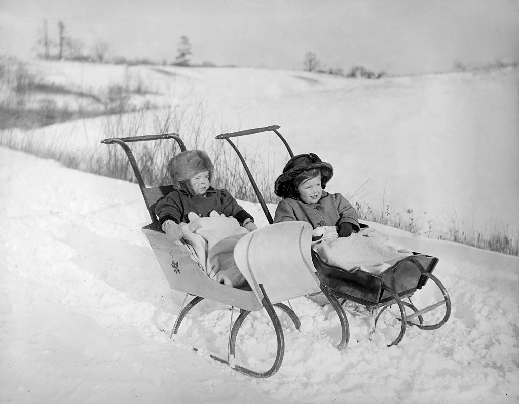 Two babies are bundled in snow strollers from the mid 20th century