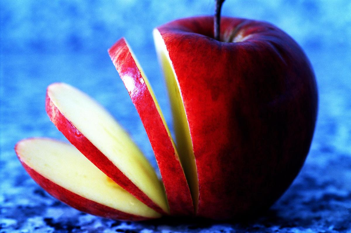 A sliced apple sits neatly on a blue surface