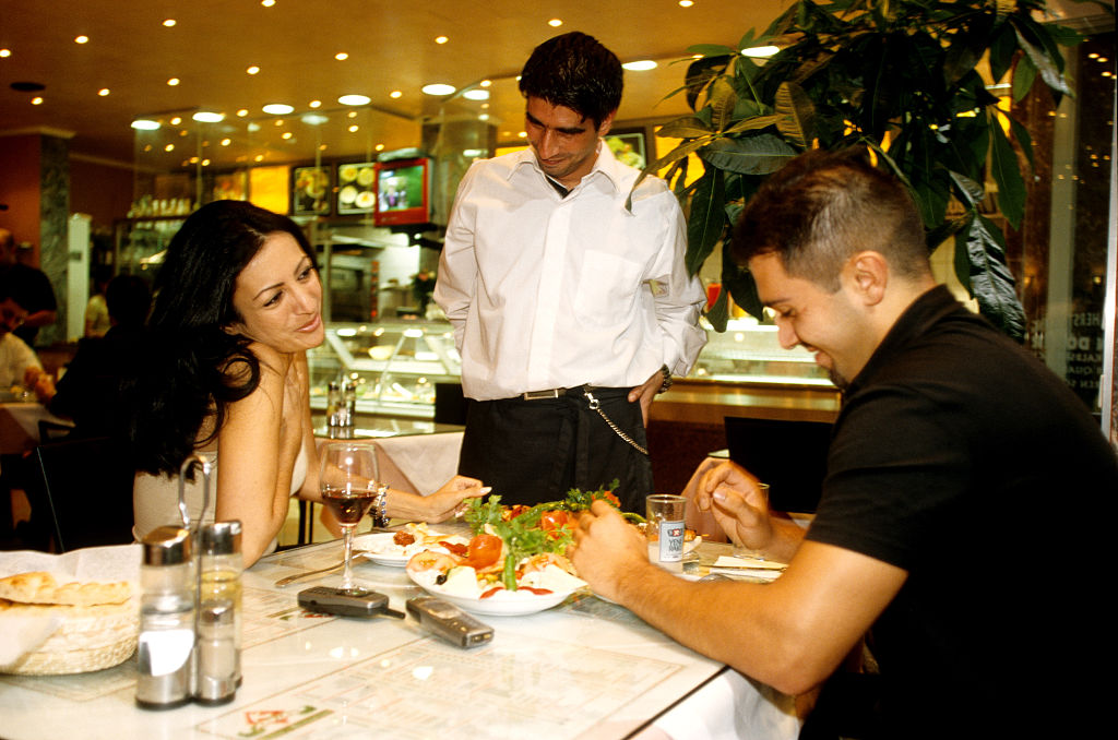A woman looks lovingly towards her partner while he orders at a restaurant