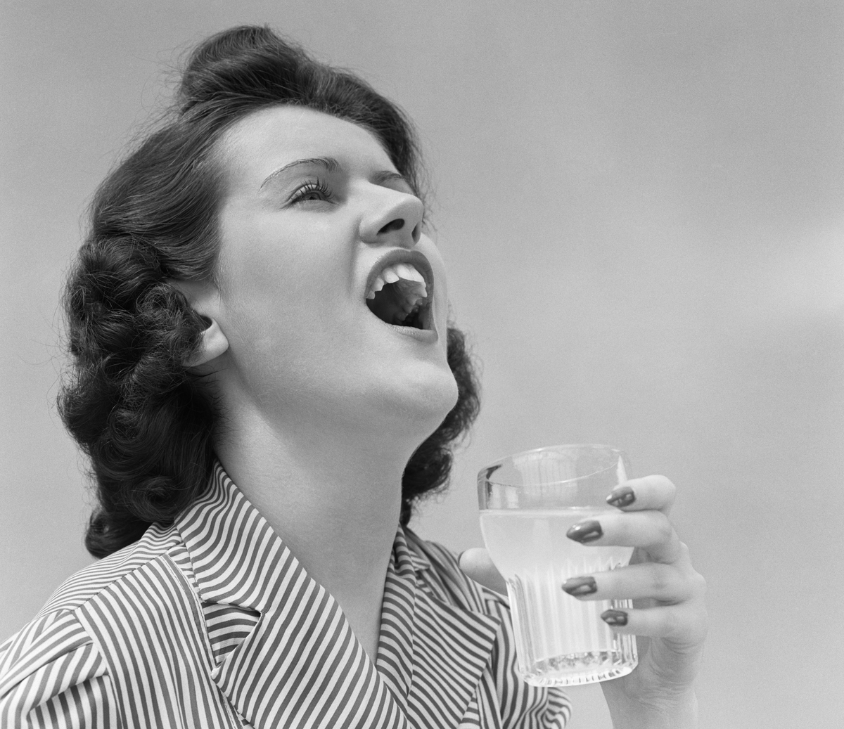 1940s WOMAN GARGLING HOLDING A GLASS
