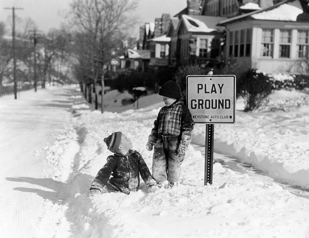 Two young boys play in the snow in front of a play ground sign