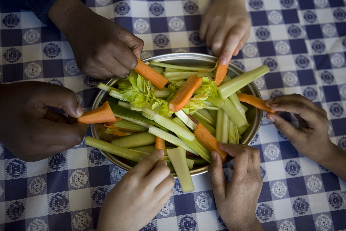 Pupils from Millfields Community School help themselves from the bowl of fresh organic carrots, cucumbers and celery