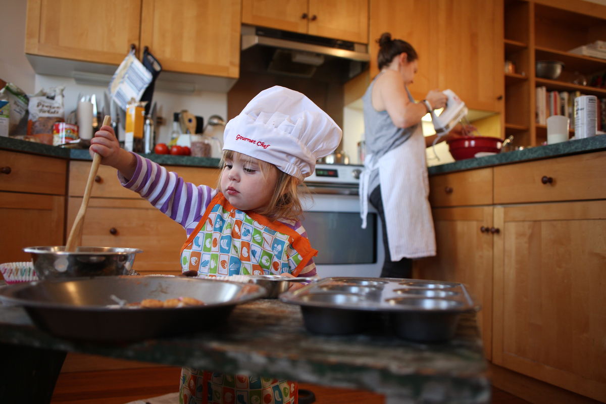 A two year old girl cooking with her mum in the kitchen as mum prepares a bake mixture.