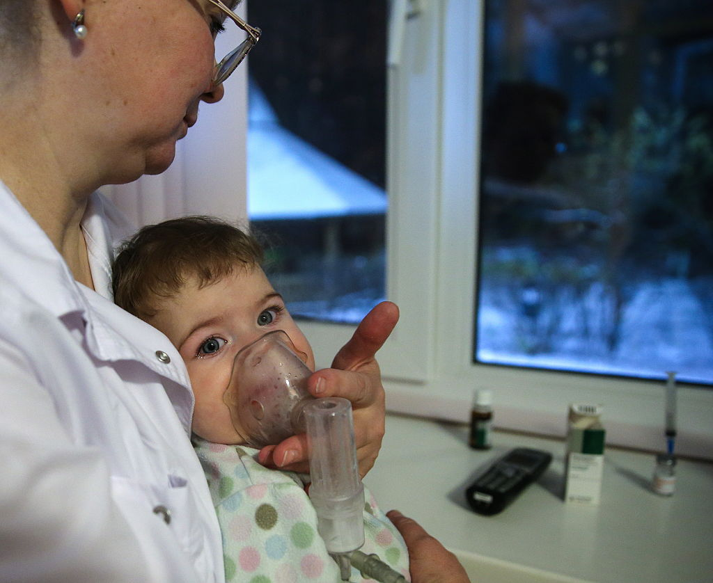A woman holds a suction mask over a baby, while snow is visible through the window.