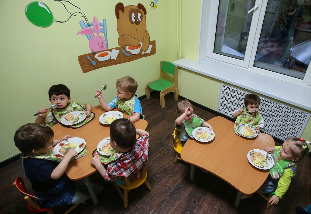 Children gather at small tables to eat at daycare