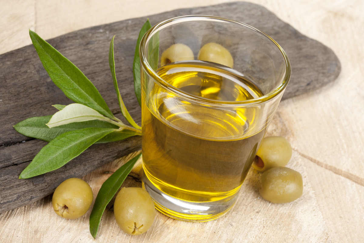Glass with olive oil and olives