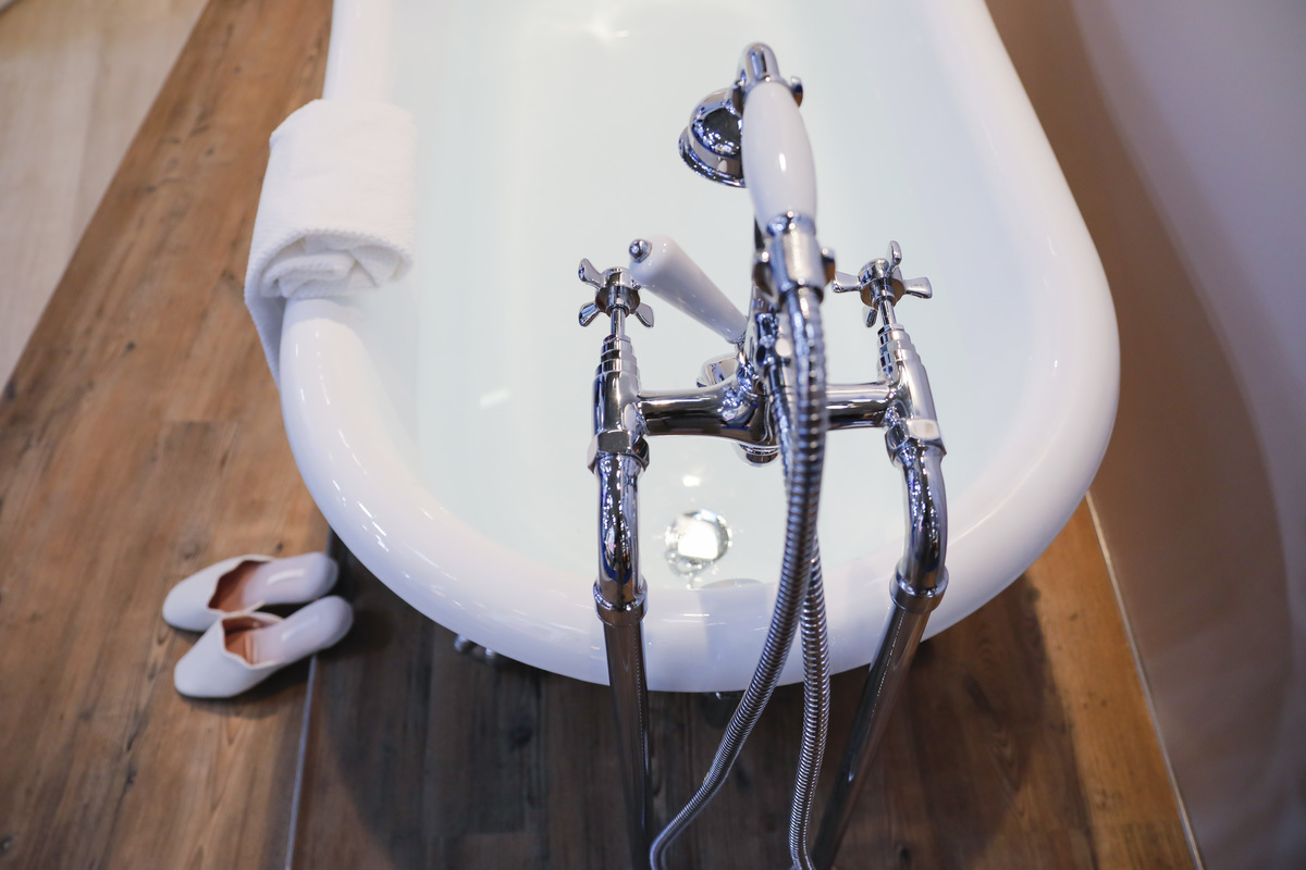 Bathtub with elegant shoes and old-fashioned water tab