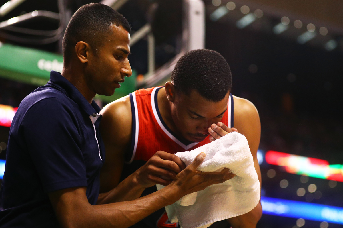 Otto Porter Jr. #22 of the Washington Wizards is tended to after getting a bloody nose