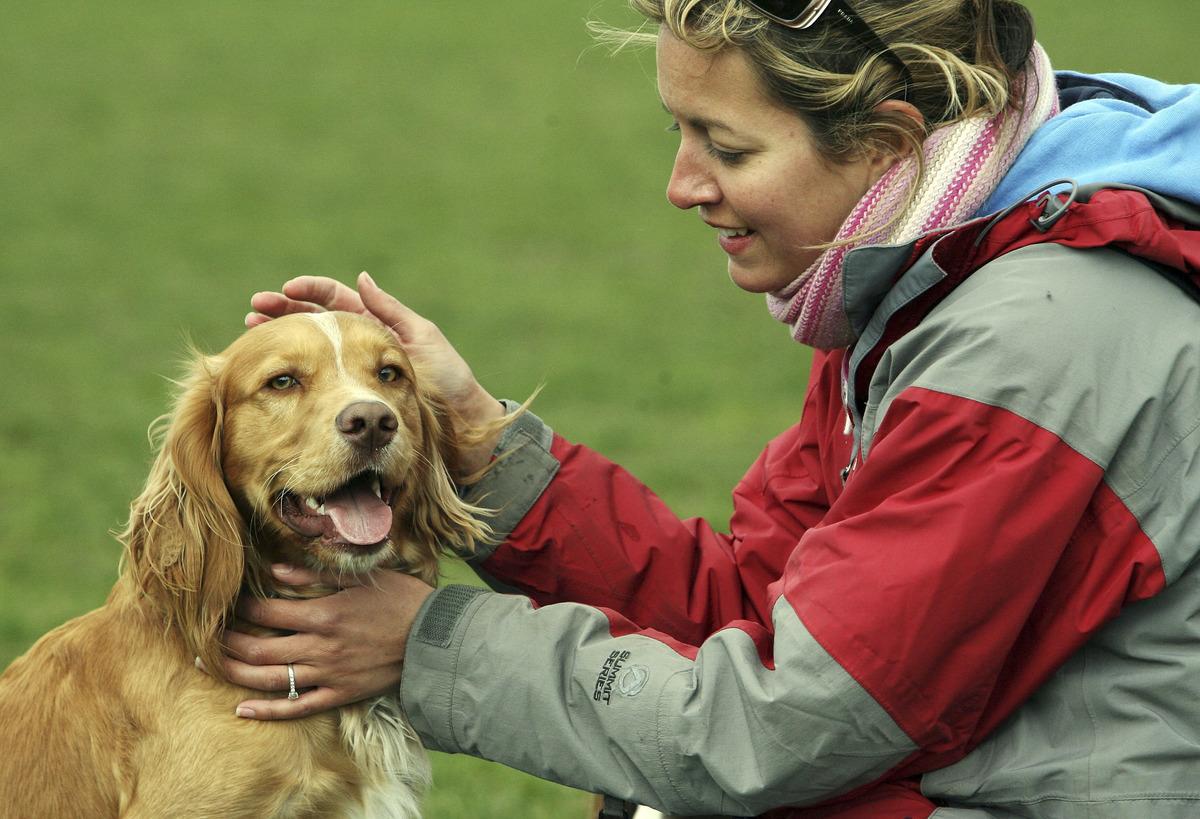 Dog owner, Fen Reilly, strokes her dog Larry in Battersea Park in London