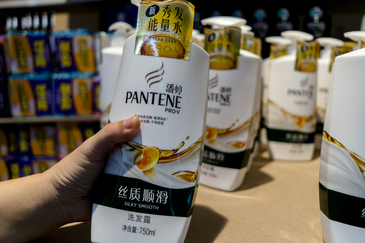 Customer chooses a Pantene shampoo in a supermarket.
