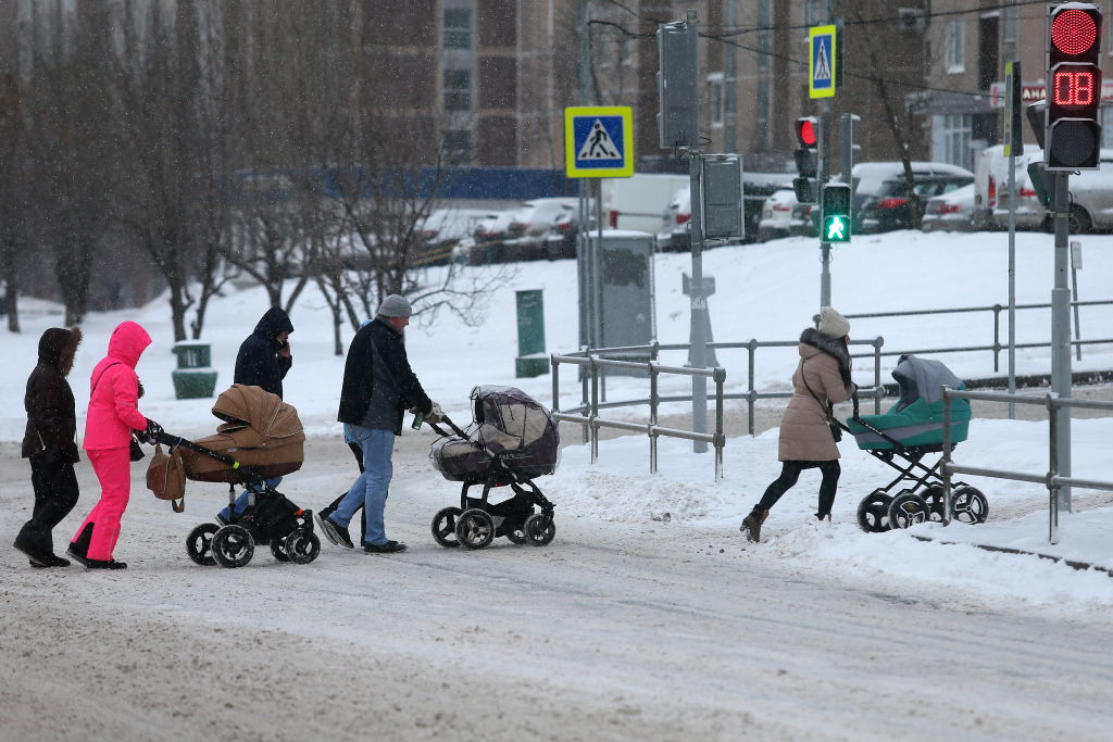 Three strollers are pushed across a snowy street