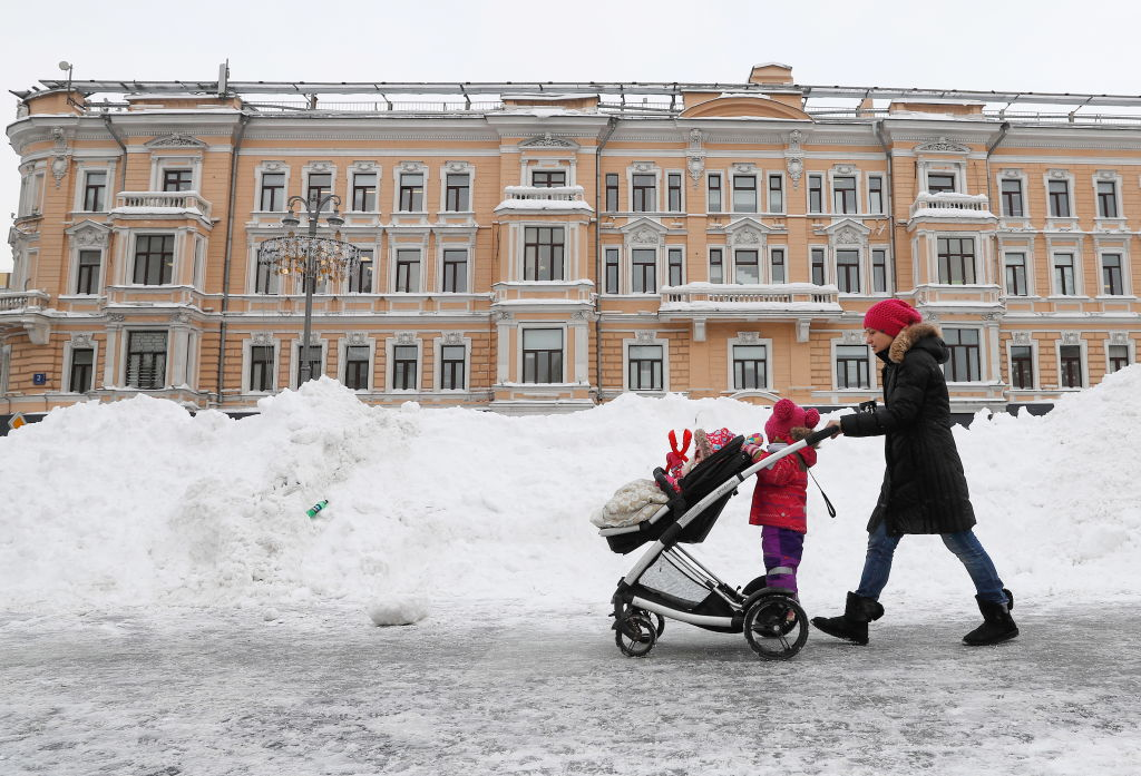 A woman pushes a stroller through the snow while a toddlers clings to the back
