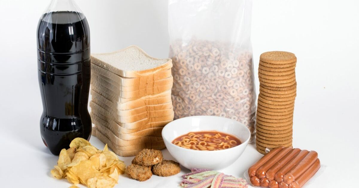 A photograph of soda, white bread, cereal, hotdogs and other unhealthy foods.