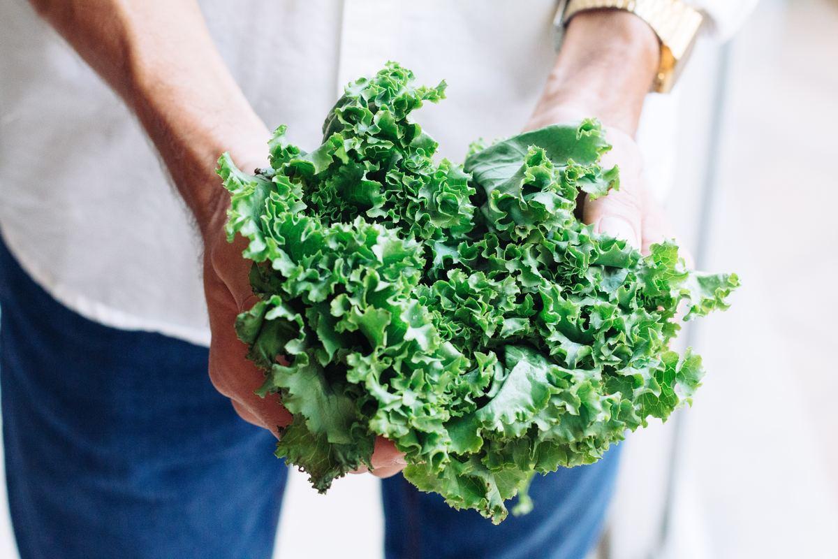 Man holds a bundle of kale