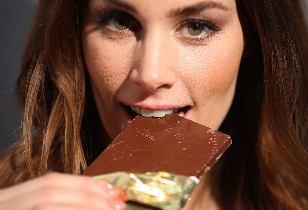 a woman biting into a chocolate bar
