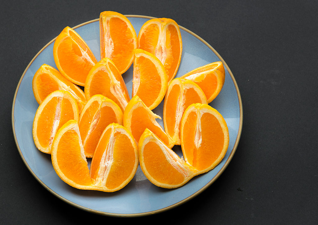 Quarter cut and unpeeled pieces of orange fruit arranged on a round blue plate