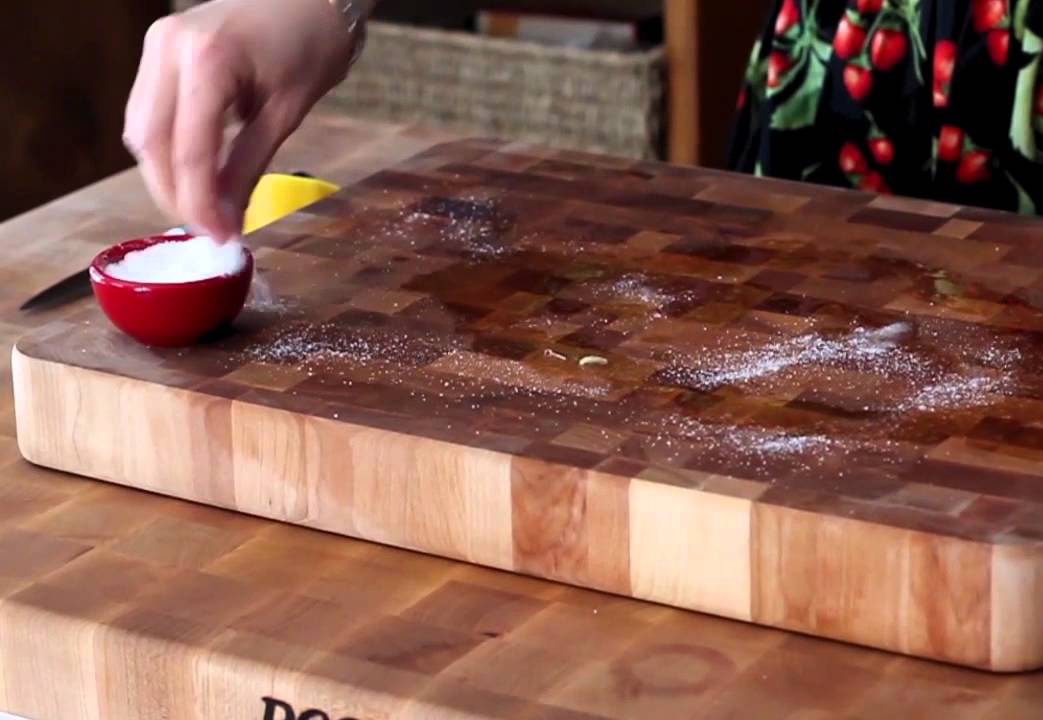 Katie Miles demonstrates how to clean a wooden cutting board with salt