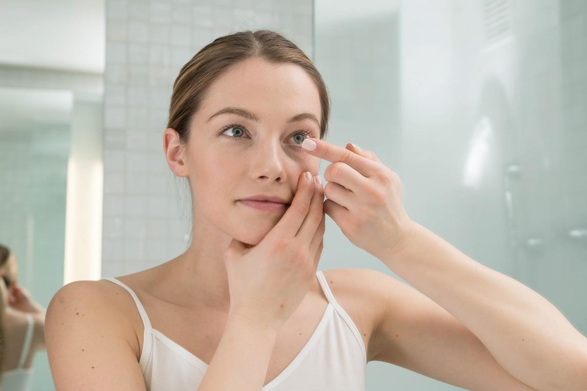 Woman puts in contact lenses