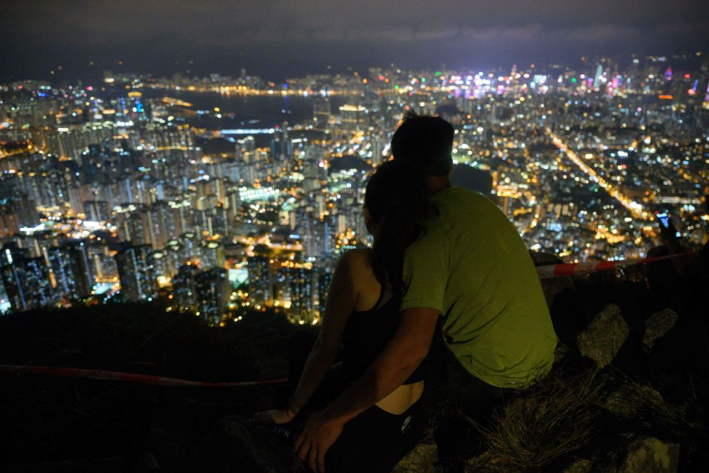 People hug on Lion Rock in Hong Kong