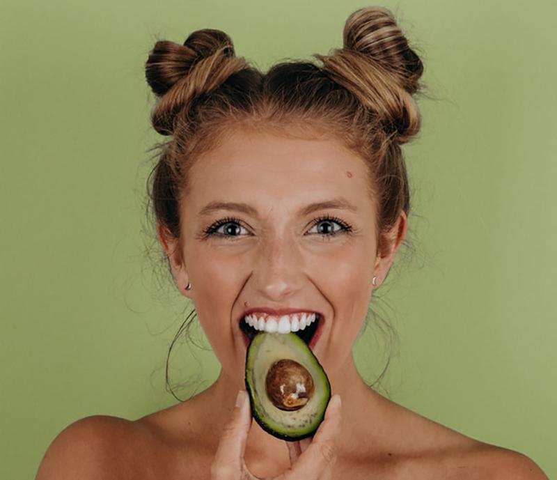 Woman happily eats an avocado in Lincoln, Nebraska