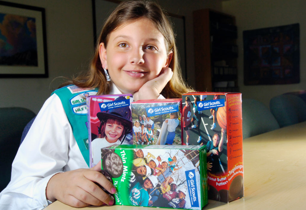 a girl scout with four boxes of girl scout cookies