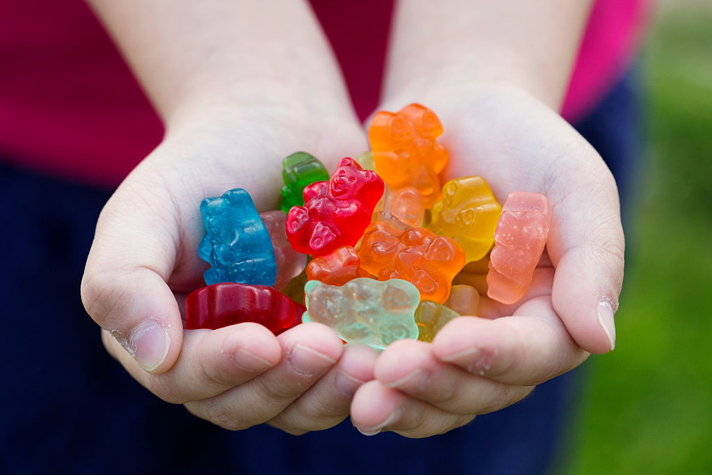 a close-up of a child holding colorful gummy bears